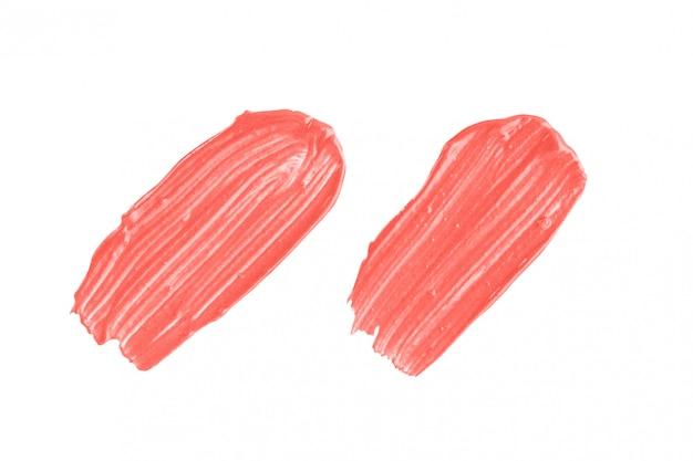Amostra de maquiagem coral. conjunto de dois traços de batom na cor da moda, isolado no fundo branco