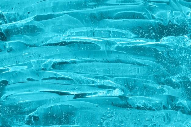 Amostra de produto para cuidados com a pele transparente transparente closeup textura de gel azul desinfetante para as mãos álcool gel