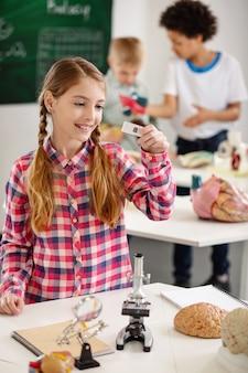 Amostra para análise. menina positivamente encantada segurando uma lâmina de microscópio enquanto a usa para sua pesquisa