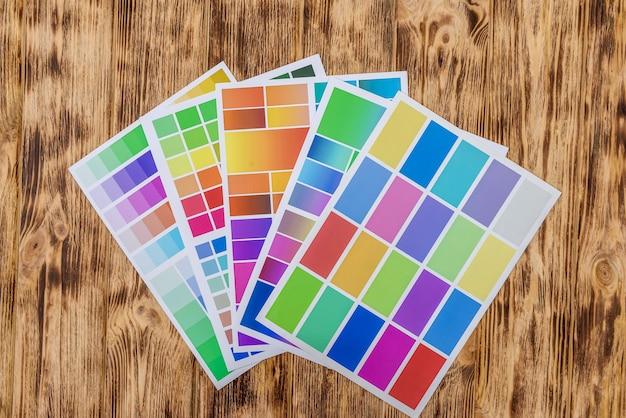 Amostradores de papel colorido na mesa de madeira.
