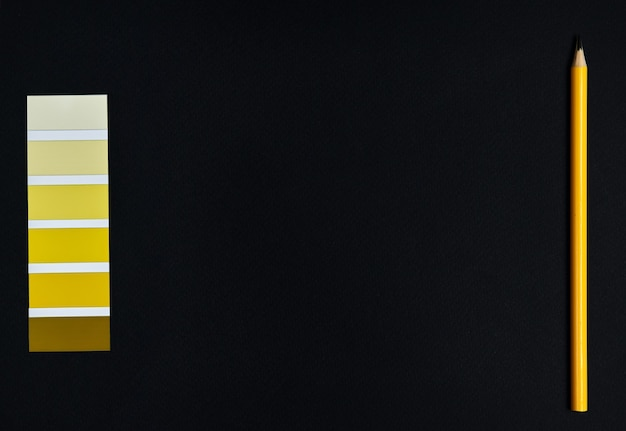 Amostras coloridas do designer e lápis de madeira em fundo preto. gradiente de amarelo. camada plana, vista superior