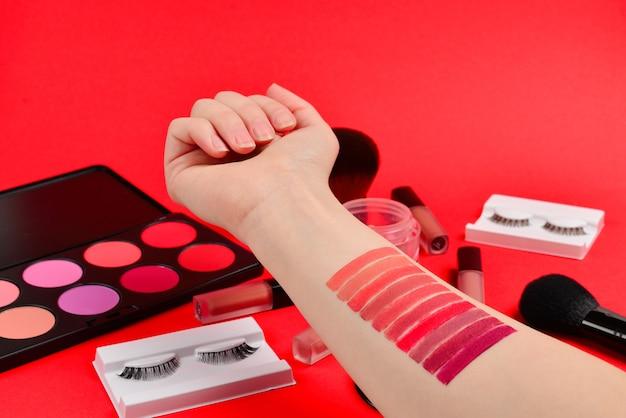 Amostras de batom na mão da mulher. produtos de maquiagem profissional com produtos cosméticos de beleza