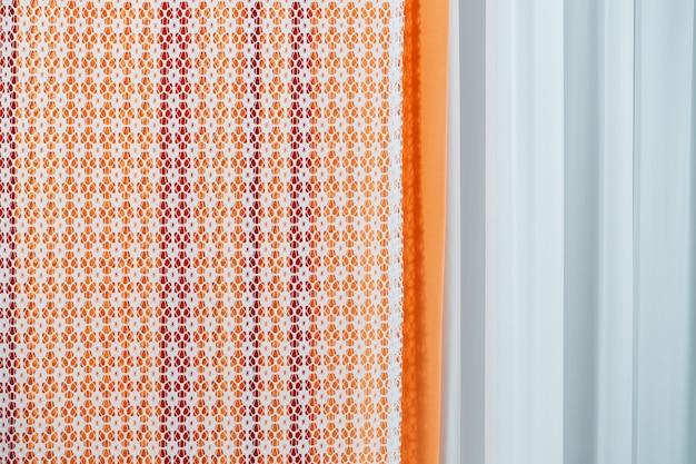 Amostras de cortina penduradas em cabides no trilho na loja. amostras de textura de tecido tecidos de seleção para decoração de interiores cortinas, tule e estofamento de móveis.