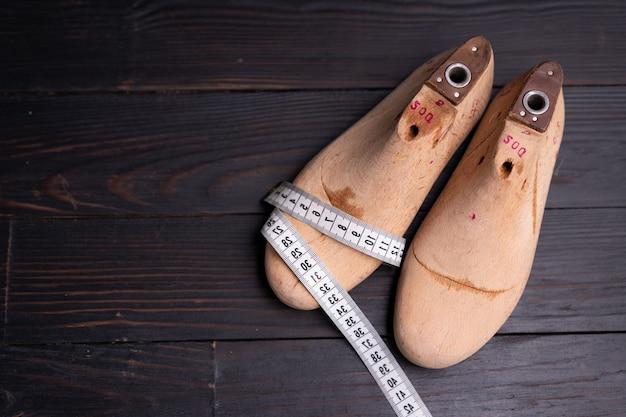 Amostras de couro para sapatos e sapato de madeira duram na mesa de madeira escura. roupas de móveis de design. espaço de trabalho do fabricante de sapatos.