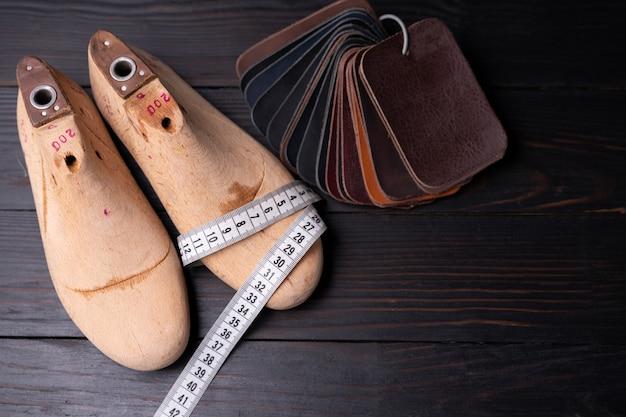 Amostras de couro para sapatos e sapato de madeira duram na mesa de madeira escura