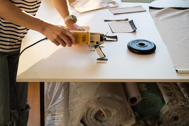 Amostras de design de roupas de alfaiate profissional com o cortador na mesa em estúdio de moda close up