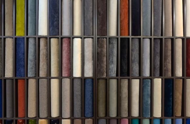 Amostras de tapetes coloridos no estande. vários designs de carpete para o interior.