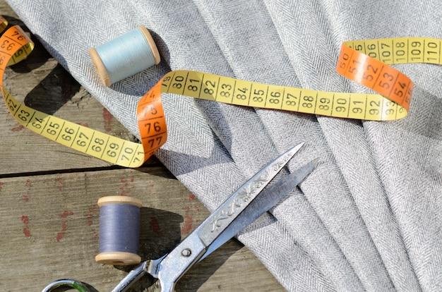 Amostras de tecido cinza terno, tesoura vintage e agulhas. pessoal de alfaiate