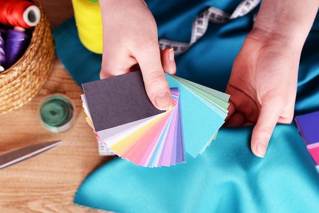 Amostras de tecido colorido em mãos femininas, close-up