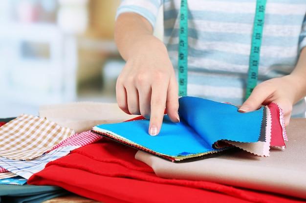 Amostras de tecido colorido em mãos femininas na mesa e a luz desfocada