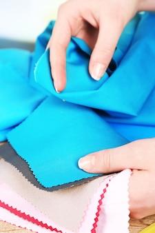 Amostras de tecido colorido em mãos femininas sobre fundo desfocado.