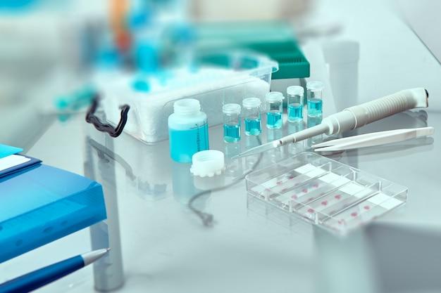 Amostras de tecido histológico coradas em vidro, tecido fixo, pipeta automática e outras ferramentas relacionadas ao trabalho