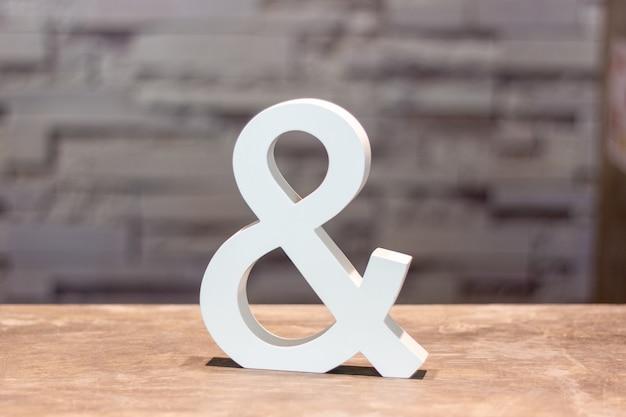Ampersand & assinar na mesa de madeira com fundo de parede turva
