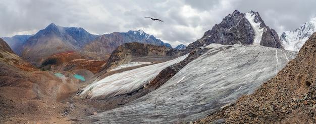 Ampla vista panorâmica do vale da montanha. paisagem montanhosa com uma enorme montanha nevada e uma geleira iluminada pelo sol entre rochas altas. impressionante cenário alpino com uma grande geleira e lagos