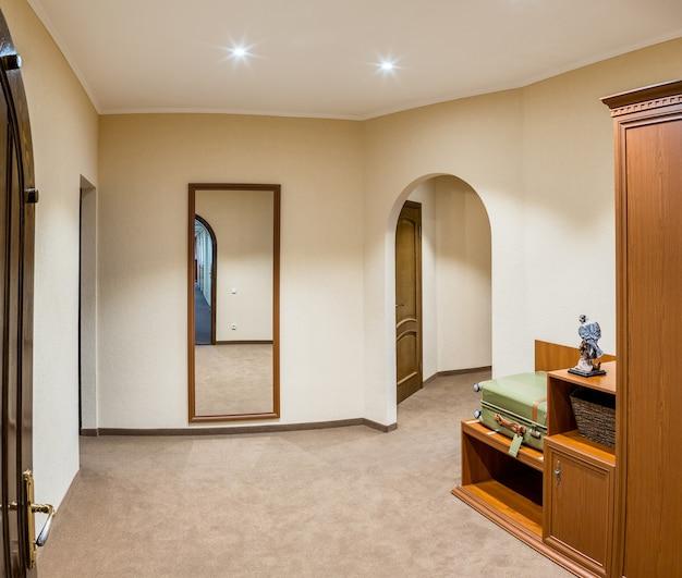 Amplo hall de entrada em quarto de hotel com mala de hóspedes em móveis de madeira
