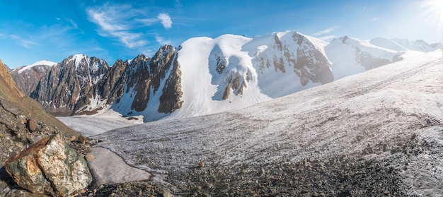 Amplo panorama do grande glaciar, no alto das montanhas, coberto de neve e gelo.