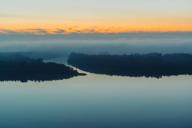 Amplo rio corre ao longo da costa com a floresta sob uma névoa espessa