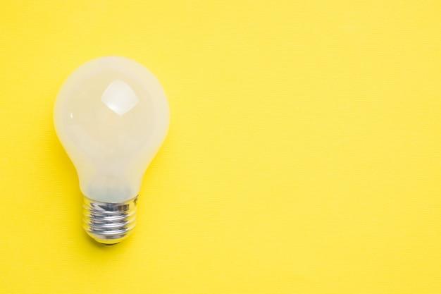 Ampola branca no fundo amarelo brilhante com foco seletivo do espaço da cópia.
