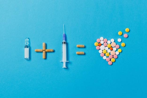 Ampola de pílulas mais agulha de seringa vazia é igual a comprimidos redondos coloridos de medicamento em forma de coração isolada em fundo azul
