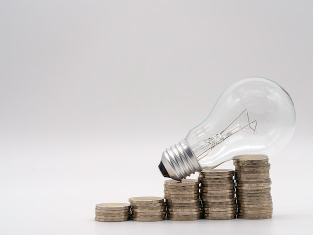 Ampola de poupança de energia com as pilhas de moedas para o conceito financeiro, de contabilidade e salvar.