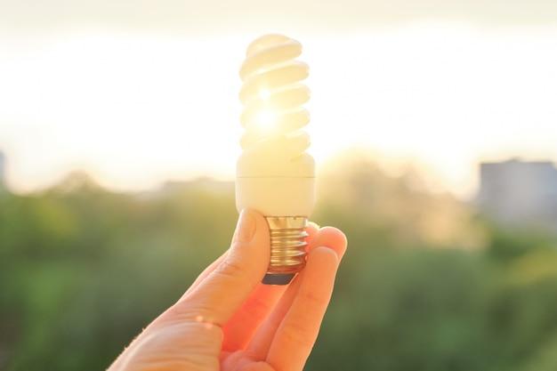 Ampola fluorescente de poupança de energia, mão que guarda a lâmpada, nivelando o fundo do céu do por do sol.