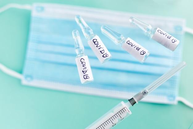 Ampolas com vacina covid-19 na superfície azul