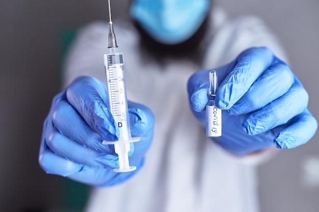Ampolas com vacina covid-19 nas mãos do médico. conceito de vacinação