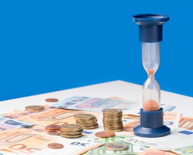 Ampulheta ao lado da pilha de moedas