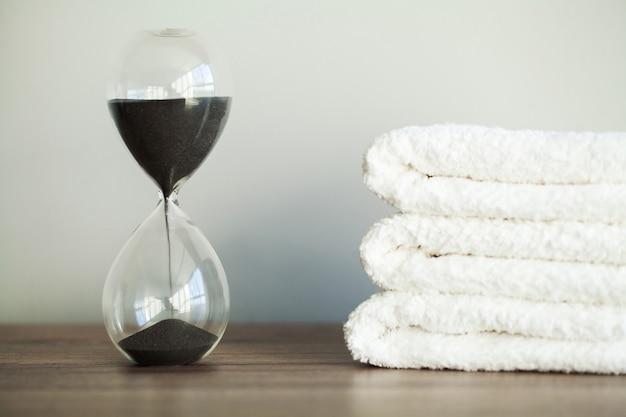 Ampulheta com areia caindo e toalhas brancas