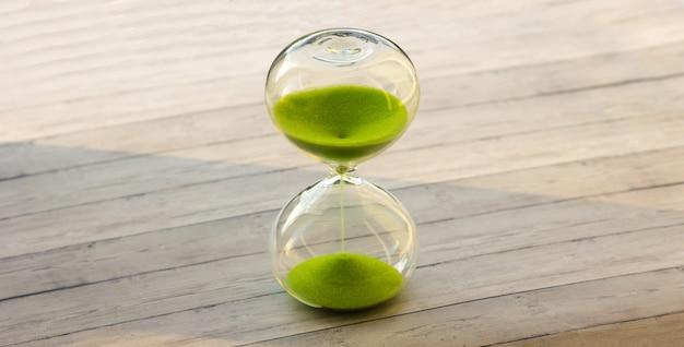 Ampulheta com areia verde em um fundo de madeira