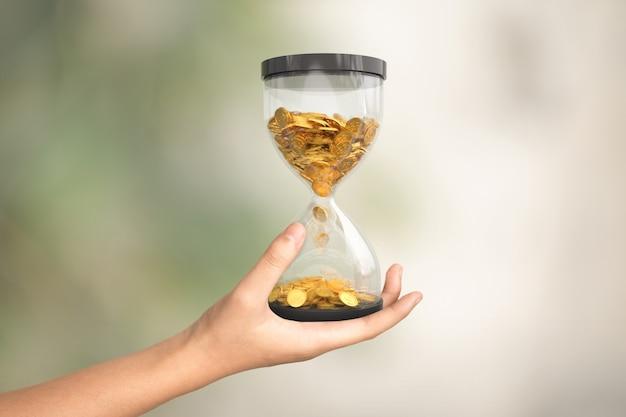 Ampulheta com moedas de ouro à mão, conceito de tempo é dinheiro