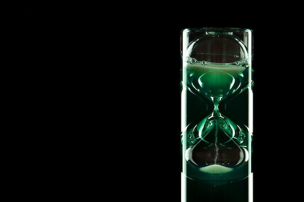 Ampulheta de design moderno com líquido colorido sobre um fundo escuro.