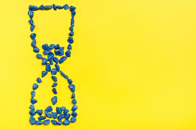 Ampulheta de pedras decorativas azuis sobre um fundo amarelo. conceito de tempo vazando