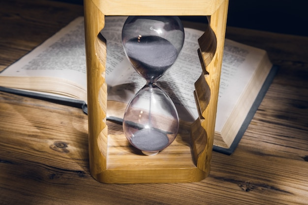 Ampulheta e livro na mesa