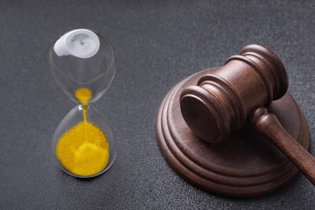 Ampulheta e martelo de juízes em preto. lei e tempo.