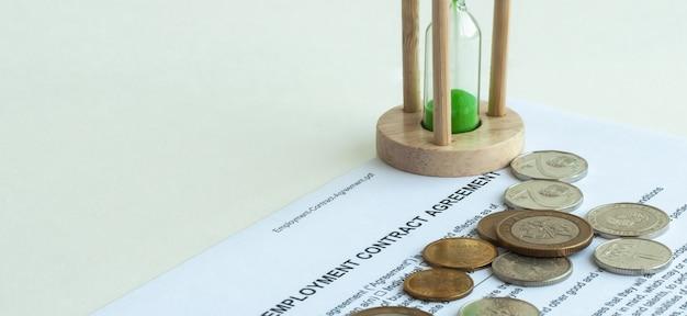 Ampulheta e moedas em um fundo branco e reflexo em uma superfície de espelho.