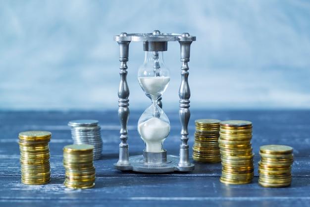 Ampulheta e moedas. tempo é dinheiro.