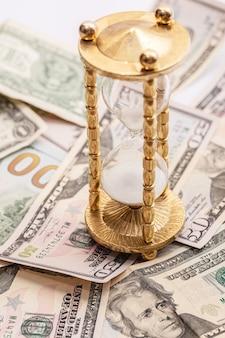 Ampulheta e notas de dólar americano. conceito de investimento ou inflação.