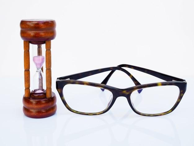 Ampulheta e óculos isolados na superfície branca, contagem regressiva de tempo para cuidar da saúde dos olhos, conceito de tempo limitado.