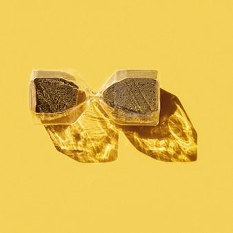 Ampulheta elegante com partículas redondas douradas
