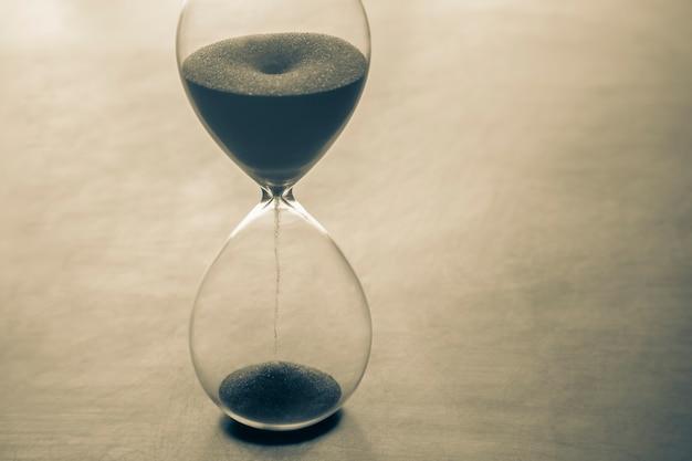 Ampulheta em um fundo escuro. tempo é dinheiro. soluções de negócios no tempo.