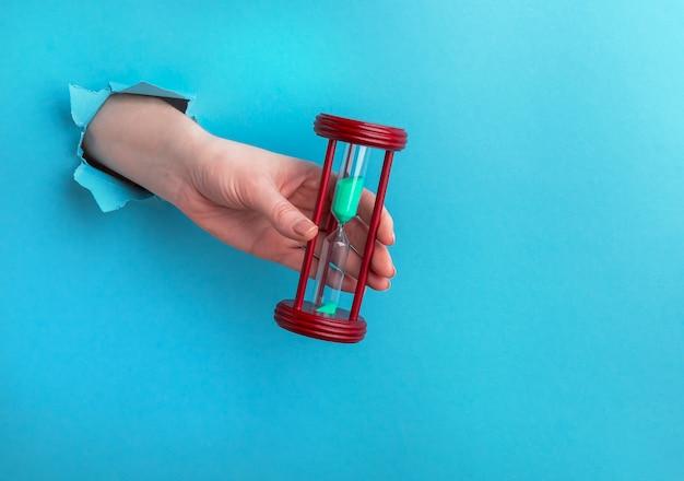 Ampulheta em uma mão feminina sobre um fundo azul com um buraco, conceito de tempo