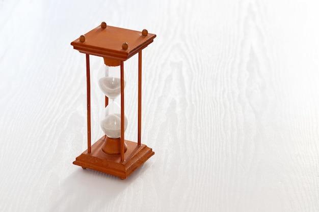 Ampulheta em uma moldura de madeira sobre uma mesa de madeira branca