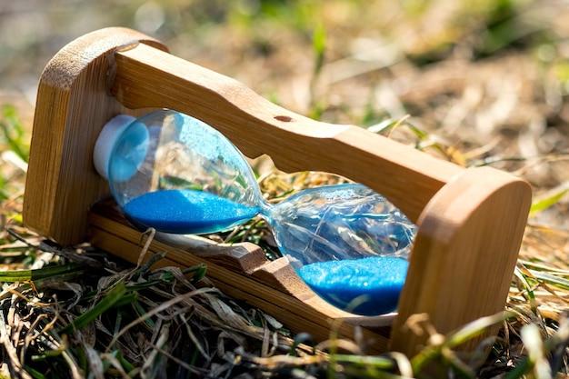 Ampulheta encontra-se na grama em tempo ensolarado. conceito de parada de tempo