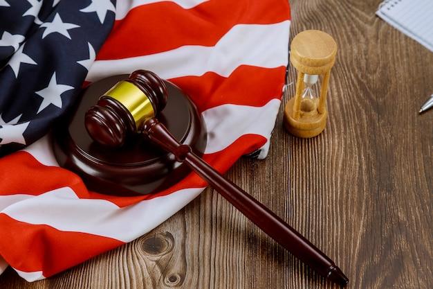 Ampulheta medindo o escritório jurídico do juiz dos eua com o martelo do juiz na tabela da bandeira americana