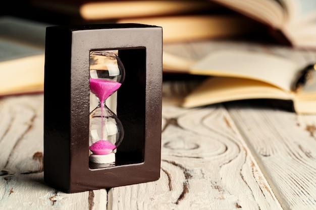 Ampulheta na mesa de madeira com livro aberto close-up