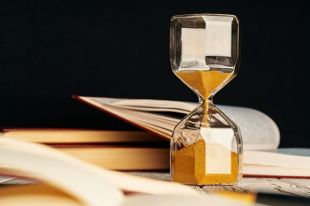 Ampulheta na mesa de madeira com livro aberto fechar