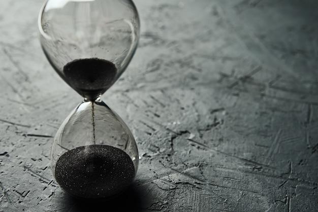 Ampulheta no escuro, close-up. urgência e conceito de tempo esgotado