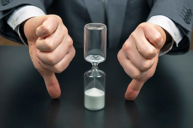 Ampulheta no espaço de um homem de negócios. distribuição do tempo de trabalho. hora de tomar decisões