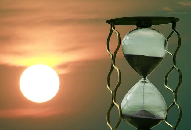Ampulheta no fundo de um pôr do sol. passagem rápida do tempo